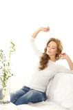A young woman stretching after being asleep Stock Photography