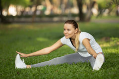 Young woman stretching in city park Royalty Free Stock Photos