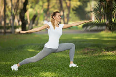 Young woman stretching in city park Stock Photo