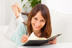 Young woman stretching comfortably on couch and reading a book Stock Photography