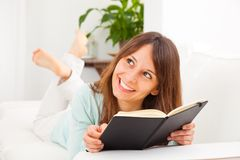 Young woman stretching comfortably on couch and reading a book Stock Photo