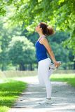 Young woman stretching on footpath Stock Photos