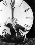A young woman stretching in front of a giant clock striking midnight Royalty Free Stock Image