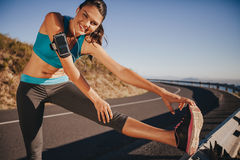 Young woman stretching on guardrail outdoors Stock Photo