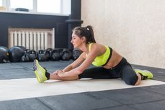 Young woman stretching hamstring in gym, fit female doing warm-up on mat stock image