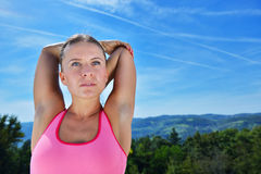 Young woman stretching her arms up while exercising on a mountain Royalty Free Stock Photo