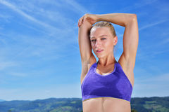 Young woman stretching her arms up while exercising on a mountain Stock Photo