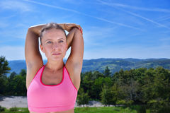Young woman stretching her arms up while exercising on a mountain Stock Images