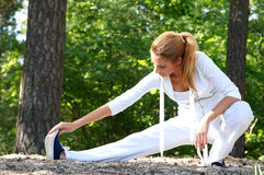 A young woman stretching her leg in the forest Stock Photo
