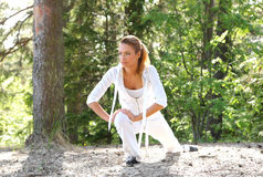 A young woman stretching her leg in the forest Royalty Free Stock Images