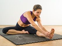 Young woman stretching her leg. Photo of a beautiful woman in the gym stretching her leg Stock Image