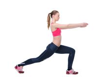 Young woman stretching leg muscles. Side view portrait of a young woman stretching leg muscles before exercise workout on isolated white background Royalty Free Stock Image