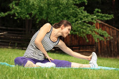 Young woman stretching legs Stock Image