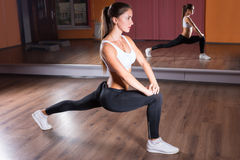Young Woman Stretching in Lunge Position in Studio Stock Photography