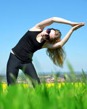 Young woman stretching on a meadow Royalty Free Stock Images