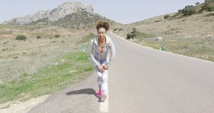 Young woman stretching among mountains stock footage
