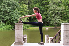 Young woman stretching outdoors in the afternoon. On Bridge. Near the river Royalty Free Stock Photo
