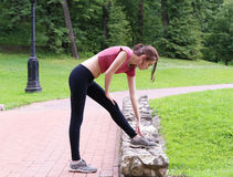 Young woman stretching outdoors. Young woman stretching outdoors in the afternoon. In the park Stock Image