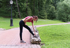 Young woman stretching outdoors in the afternoon. In the park Royalty Free Stock Photo