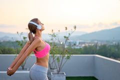 Young woman stretching outdoors. Music and fitness. Young woman in sports wear with headphones stretching outdoors Royalty Free Stock Photography