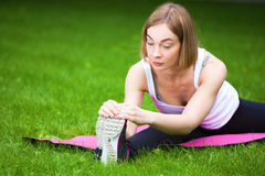 Young woman is stretching in the park. Royalty Free Stock Image