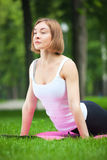 Young woman is stretching in the park. Stock Photos