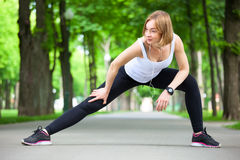 Young woman stretching in the park. Royalty Free Stock Photography