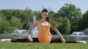 Young woman stretching in a park. stock video