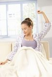 Young woman stretching in pyjama Stock Photography