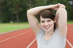 Young woman stretching on running track Royalty Free Stock Image