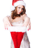 Young woman stretching santa hat to get a gift Stock Photos