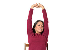 Young woman stretching with a smile of pleasure. Raising her arms above her head Stock Image