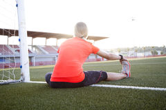 Young Woman Stretching on a Soccer Field Stock Photography