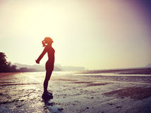 Young woman stretching on sunrise beach Royalty Free Stock Images