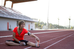 Young Woman Stretching on a Track Before a Run Stock Images