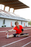 Young Woman Stretching on a Track Before a Run Royalty Free Stock Photo