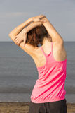 Young woman stretching triceps on the beach Stock Photos