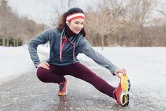 Young woman stretching and warming up for jogging outside in winter park