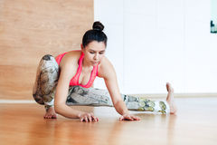 Young woman stretching and warming up before working out at a yoga Royalty Free Stock Photography