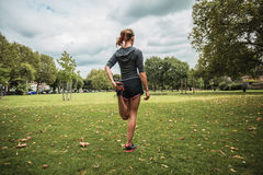 Young woman stretching and working out in park Stock Photos