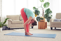 Young woman stretching on yoga mate in living room royalty free stock photos