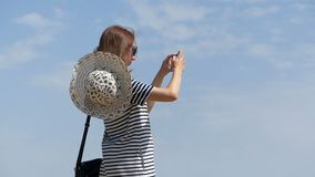 Young woman in a striped dress shoots outdoors in slo-mo. An original view of a young woman in a striped dress who shoots outdoors with her mobile phono on a stock video
