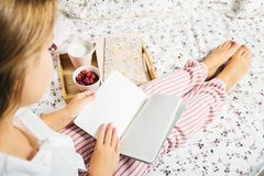 Young woman in pajamas keeps an open notebook at home in bed, top view royalty free stock image