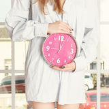 Young woman in striped shirt holding pink alarm clock Stock Photography