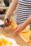 A young woman in a striped shirt making a yellow paper flower with scissors. Handmade design for home. Hobby as art Stock Images
