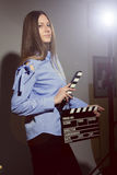 Young woman in a striped shirt with movie clapper. Royalty Free Stock Photography
