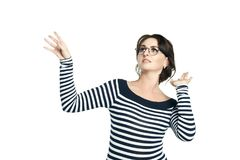 A young woman in a striped tight blouse and in glasses. She waves away from something unpleasant as from flies. Isolated on white background. to wave hands stock photography