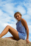 Young woman in striped vest sits on a rock Royalty Free Stock Photography