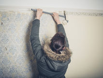 Young woman stripping wallpaper Royalty Free Stock Photos