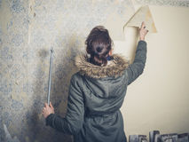 Young woman stripping wallpaper Royalty Free Stock Images